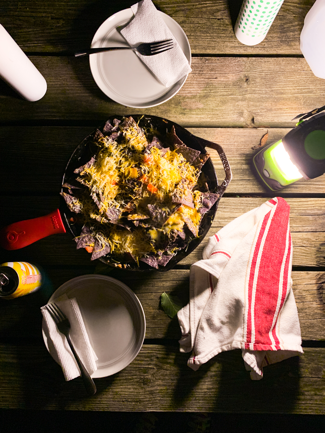 nachos in a cast iron skillet at night while camping on a picnic table