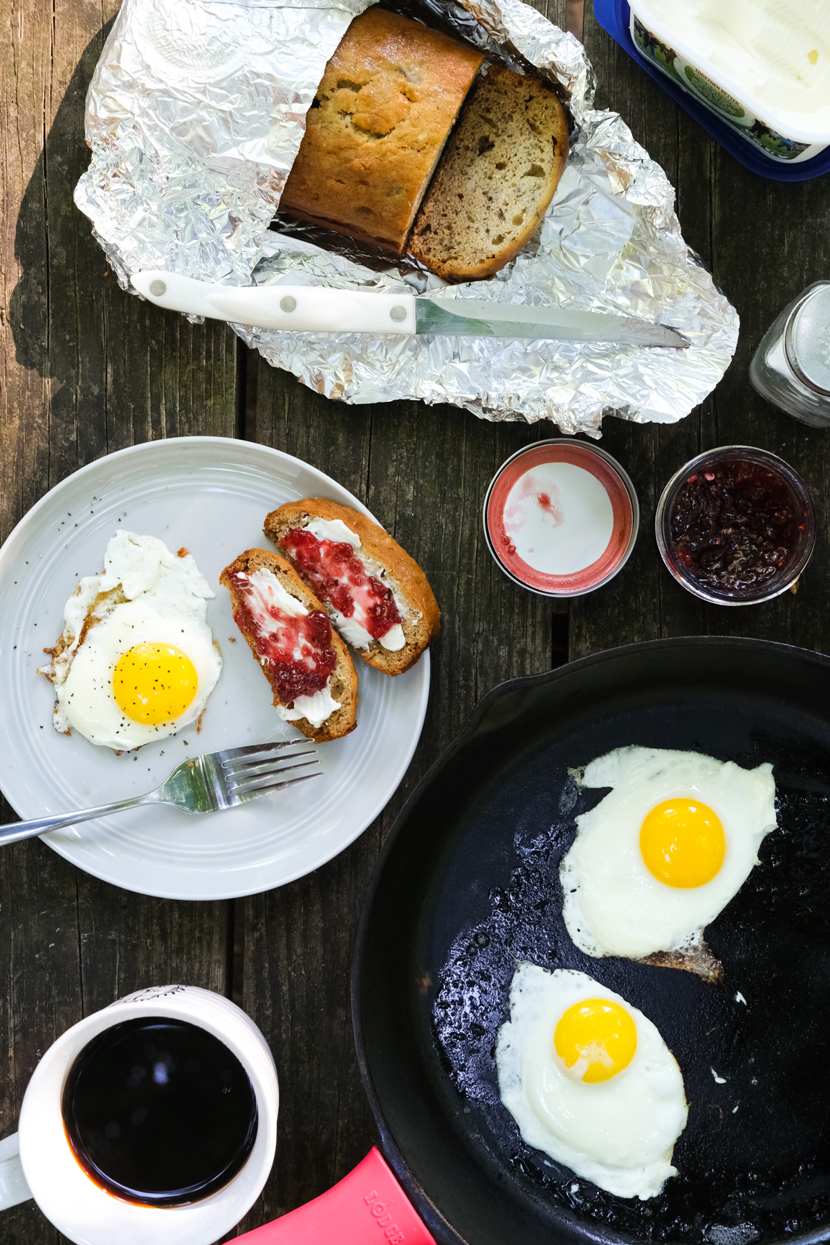 eggs and banana bread with jam and coffee on a picnic table