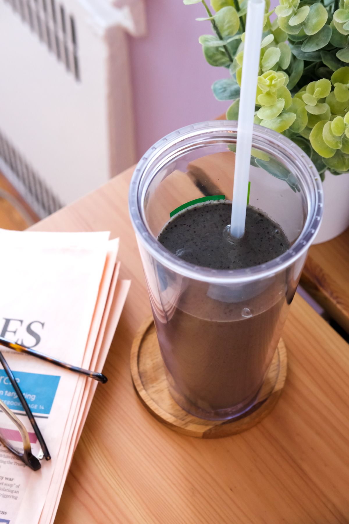 blueberry superfood smoothie on a desk with a newspaper and glasses