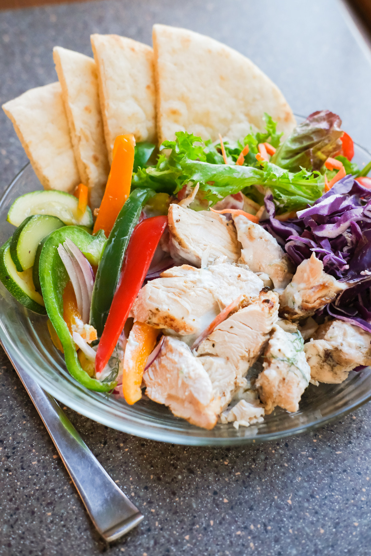greek chicken in a bowl with pita and fresh cut vegetables
