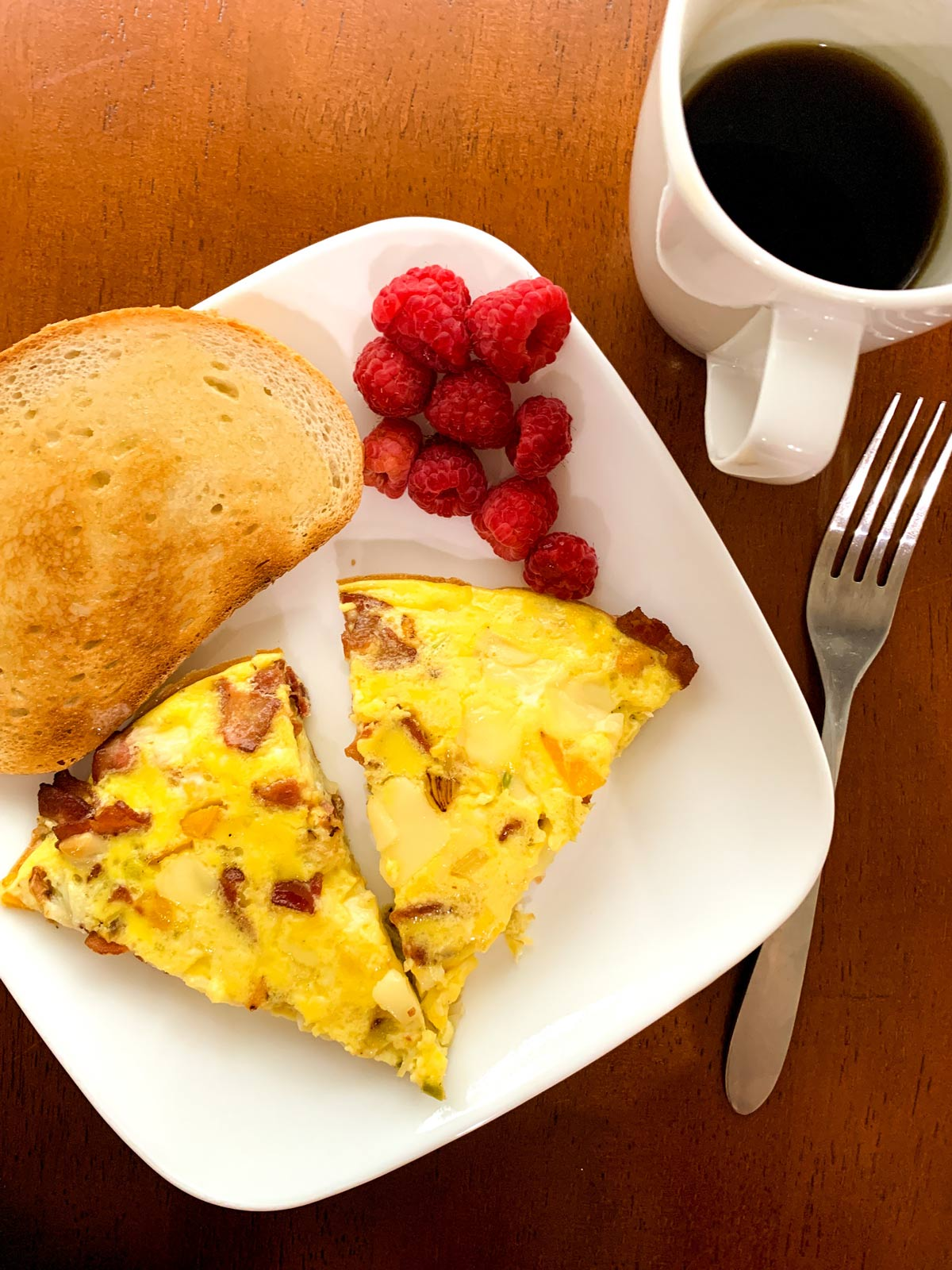 slices of frittata on a plate with toast and berries