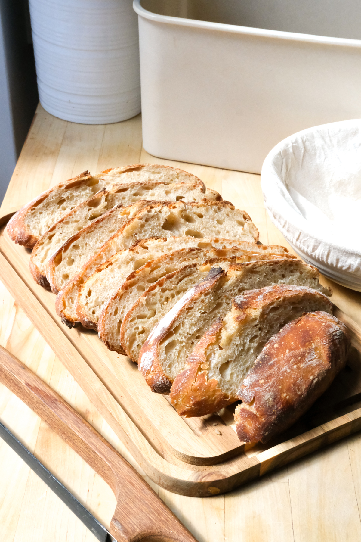 sourdough bread on a cutting board with bread tools