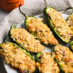 baked jalapeno poppers on a plate with cans of beer