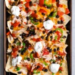 sheet pan with chicken nachos topped with fixings and sour cream