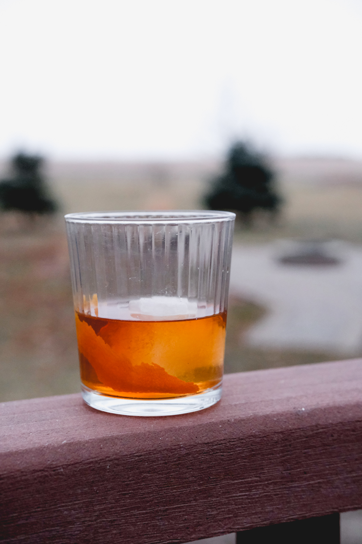 old fashioned cocktail outside on a patio ledge