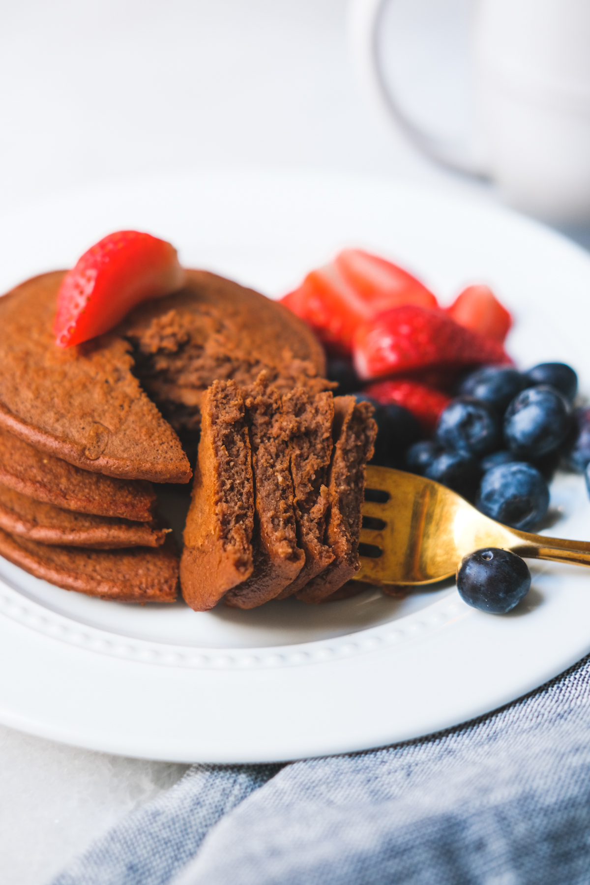 forkful of chocolate protein pancakes with berries on a plate
