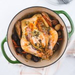 dutch oven roast chicken with herbs and potatoes and carrots on a table