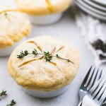 mini chicken pot pies in ramekins with thyme garnished on top