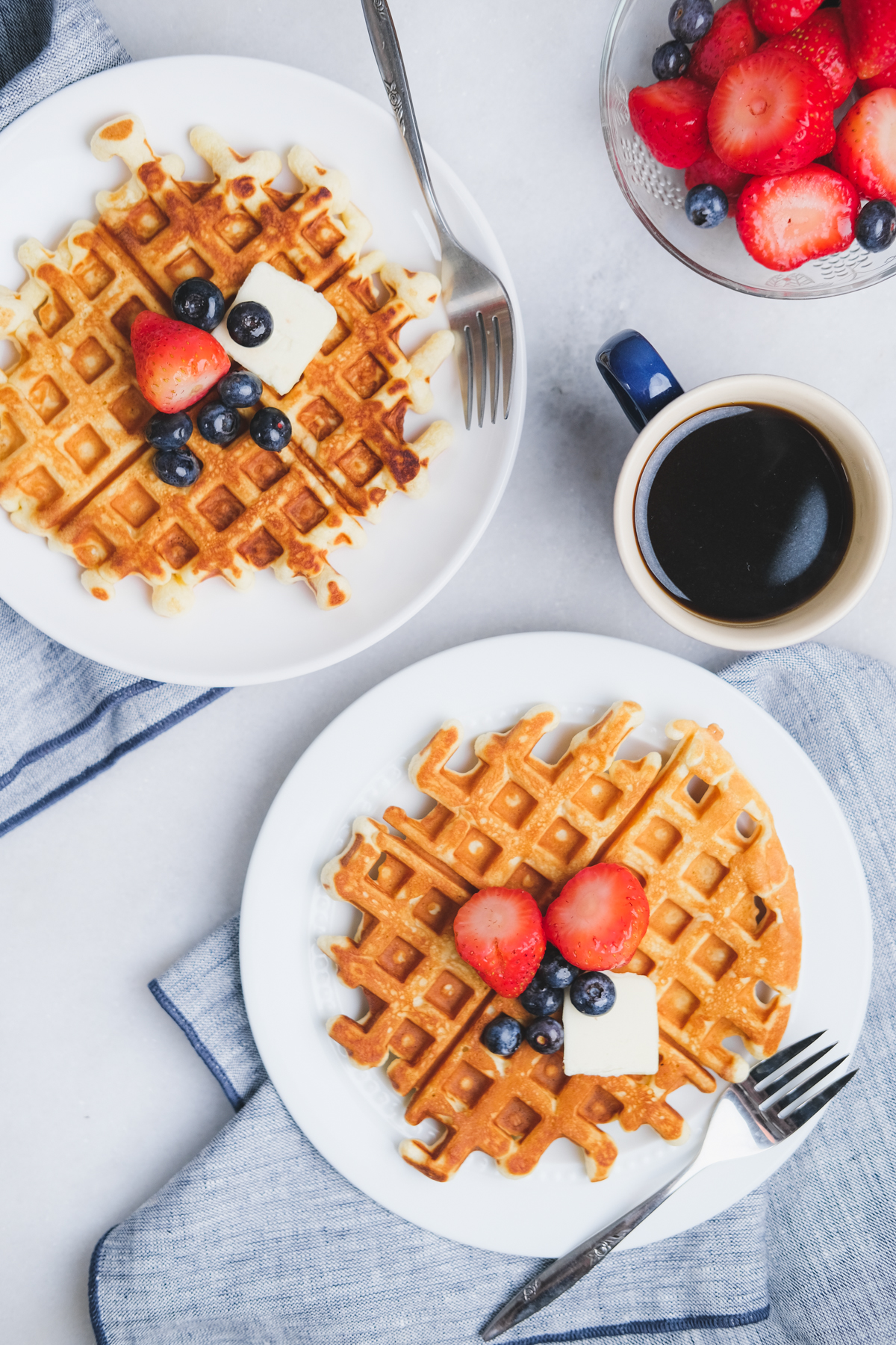old fashioned waffles with berries and butter on a breakfast table