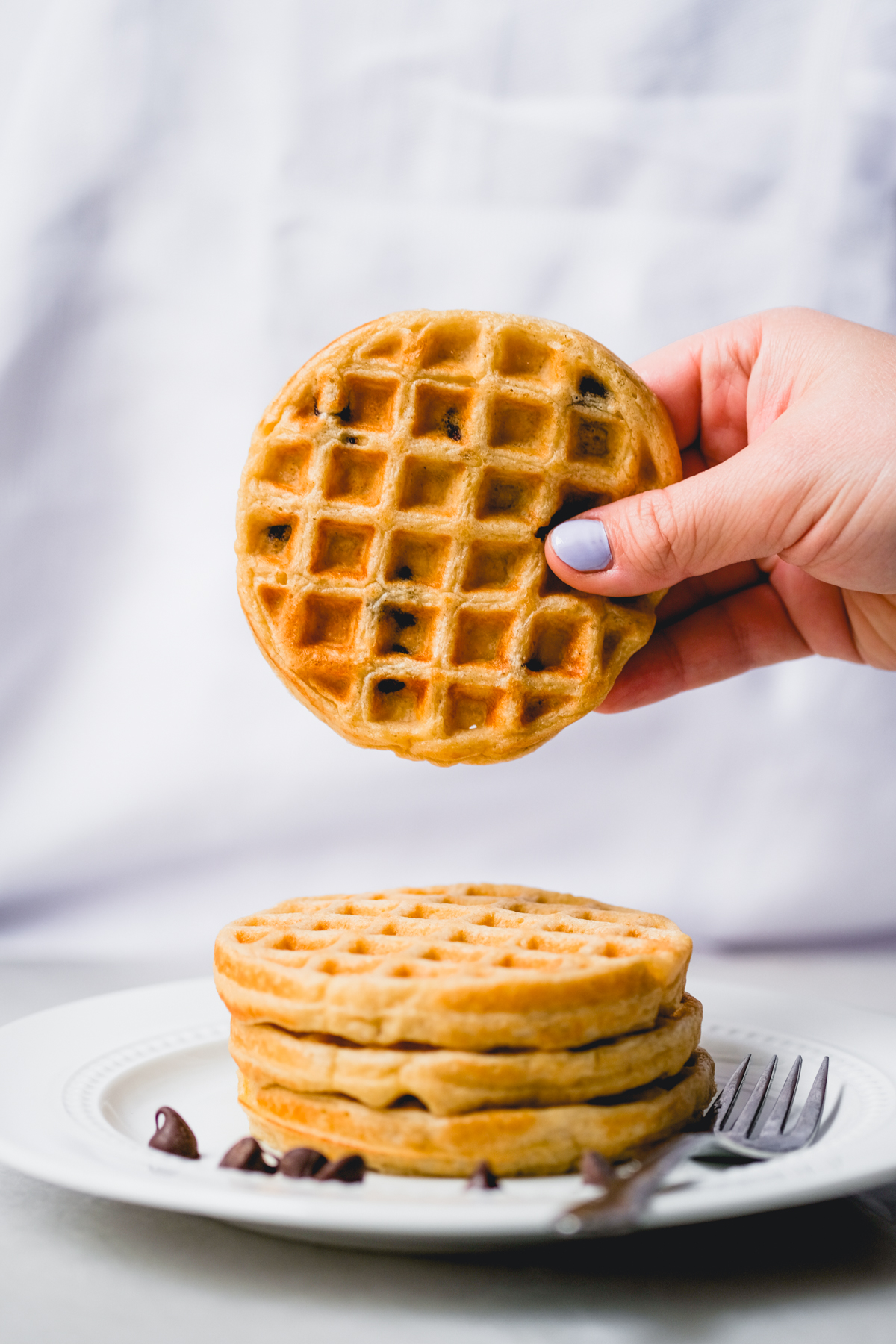 holding a mini chocolate chip oat waffle above a stack on a plate