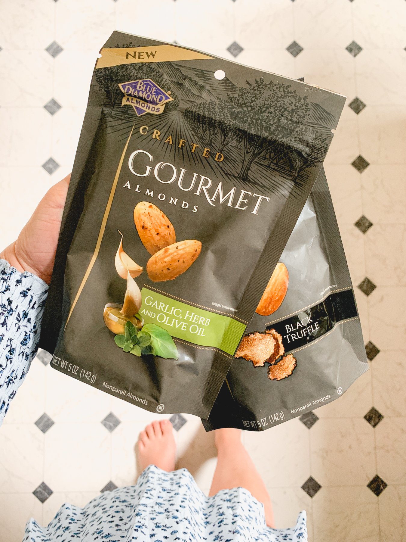 holding two bags of blue diamond gourmet almonds