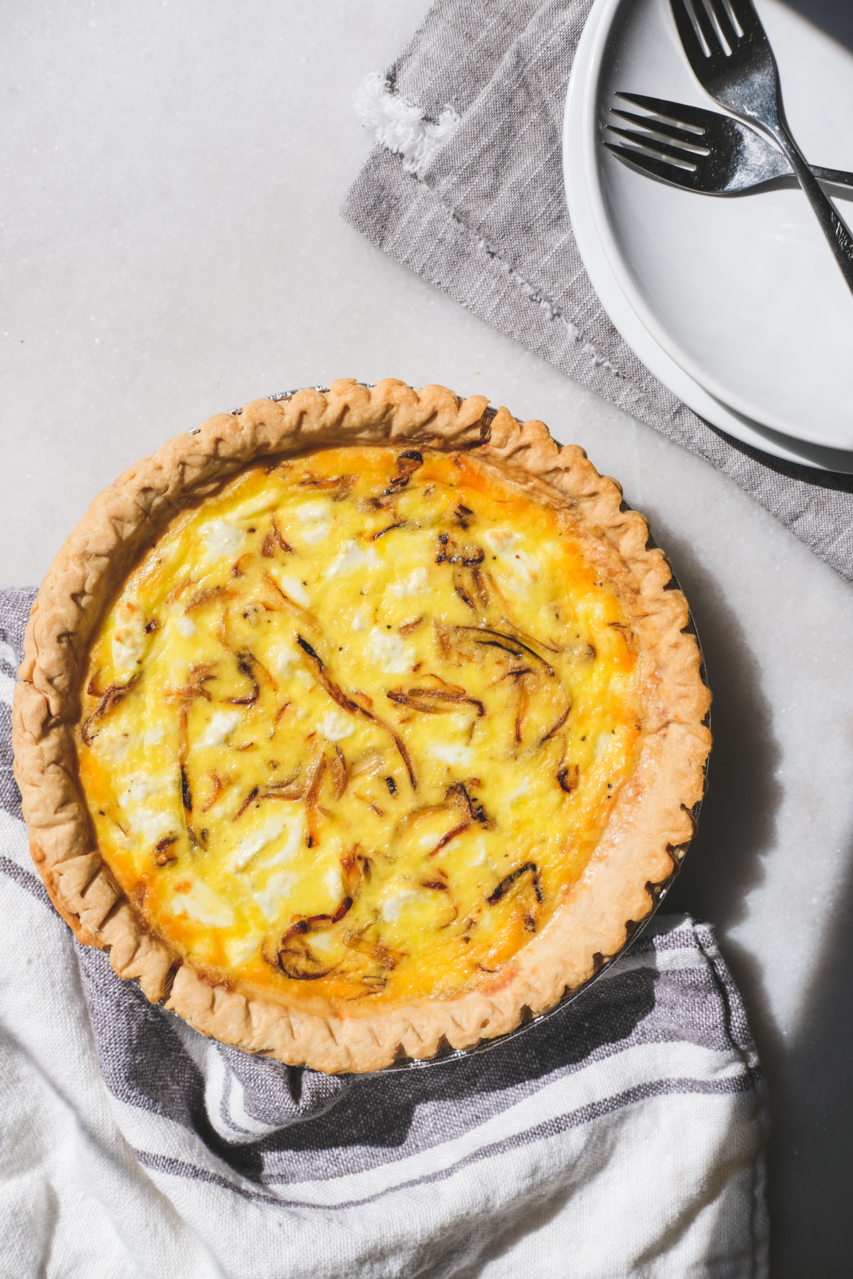 caramelized onion and goat cheese quiche on a breakfast table with plates and forks