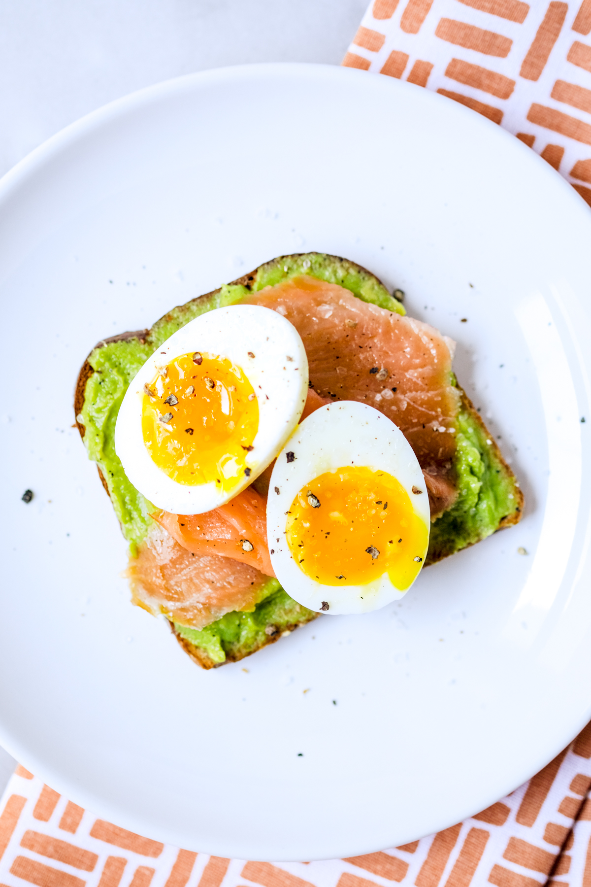 smoked salmon avocado toast with a soft boiled egg and fresh cracked pepper