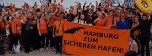 """Demonstrierende, orange gekleidete Menschen mit Transparent """"Hamburg zum sicheren Hafen machen"""""""
