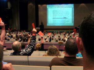 Ein großer Sitzungssaal mit einigen Personen, welche zur Abstimmung ihre Stimmkarten in die Luft halten. Mitglieder des FC St. Pauli bei einer Abstimmung während der Jahreshauptversammlung.