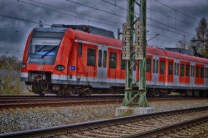 Zu sehen ist eine rot-graue S-Bahn auf einer mehrgleisigen Bahnstrecke