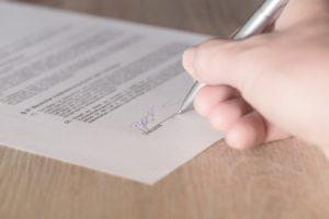 Jemand signiert einen Vertrag. Zu sehen ist nur der Zettel mit dem Vertrag sowie eine rechte Hand mit einem Stift