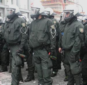 Mehrere Polizisten in massiver Schutzausrüstung und mit Pfefferspray bewaffnet