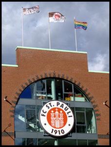 Südliches Portal vom Millerntor-Stadion mit Vereinslogo und drei Flaggen (Kiezhelden, FC St. Pauli, Regenbogenfahne)