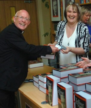 Fr Tommie Towey receives his copy at the book launch in the Newman Institute from Anne Sweeney.