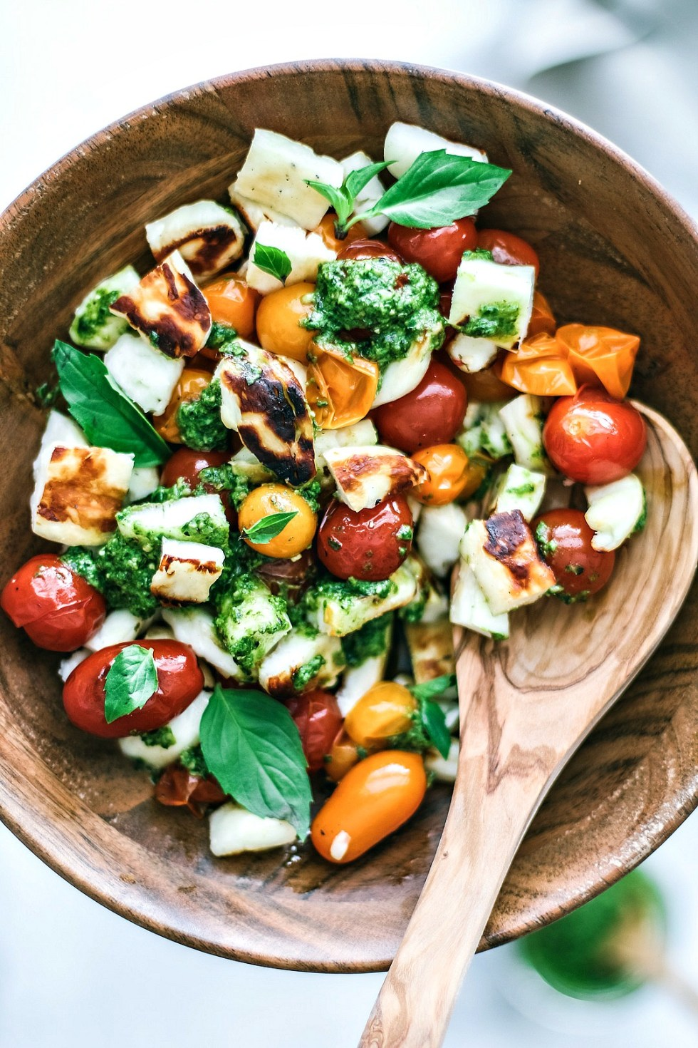 Grilled Halloumi and Burst Tomato Salad With Pesto in a bowl
