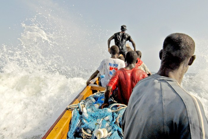 Fishermen in small boat with nets in shaky water