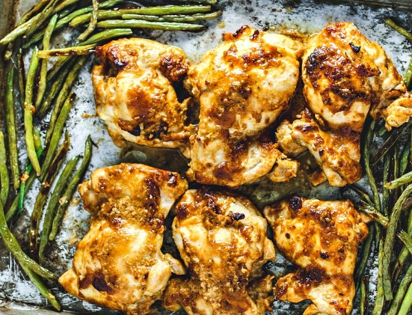 Chicken Thighs slathered in peanut sauce on a sheet pan with green beans.