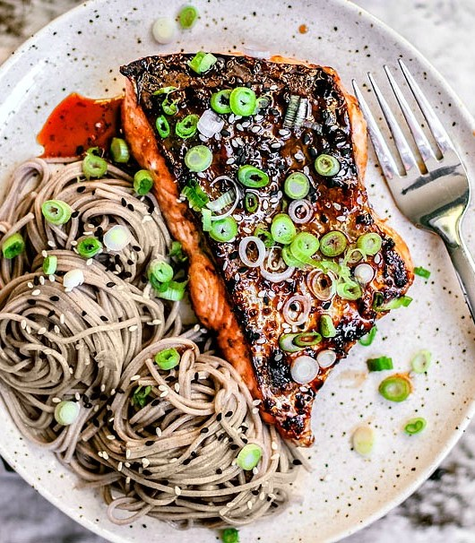 Hot Honey and Soy Salmon on a plate with soba noodles and scallions.
