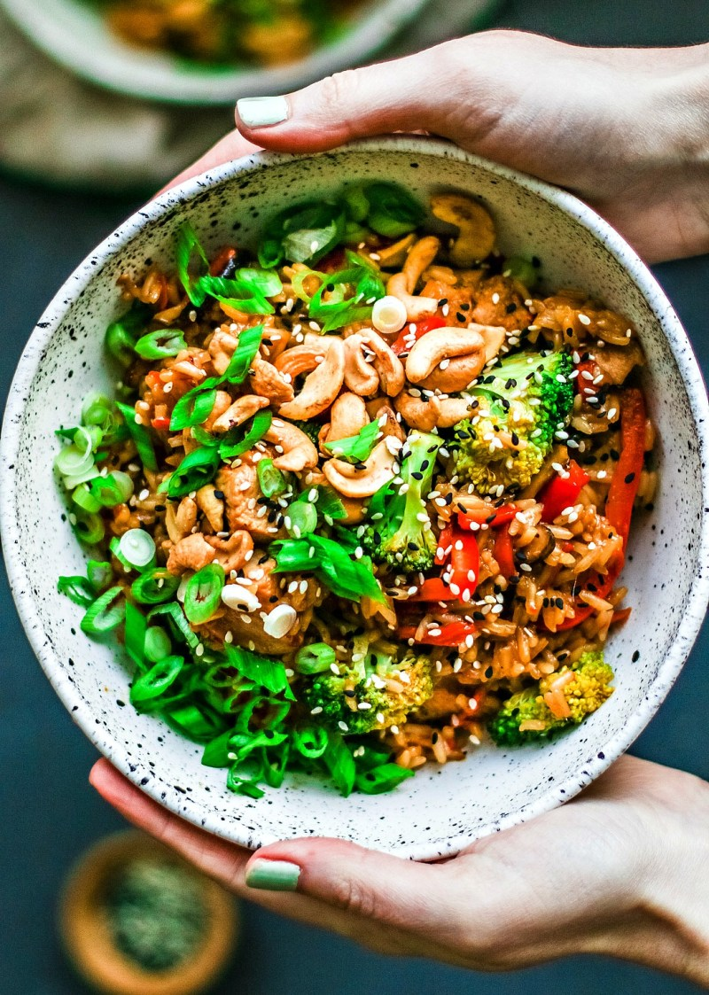 Hands holding bowl of Honey Garlic Chicken and Rice, loaded with veggies and cashews.