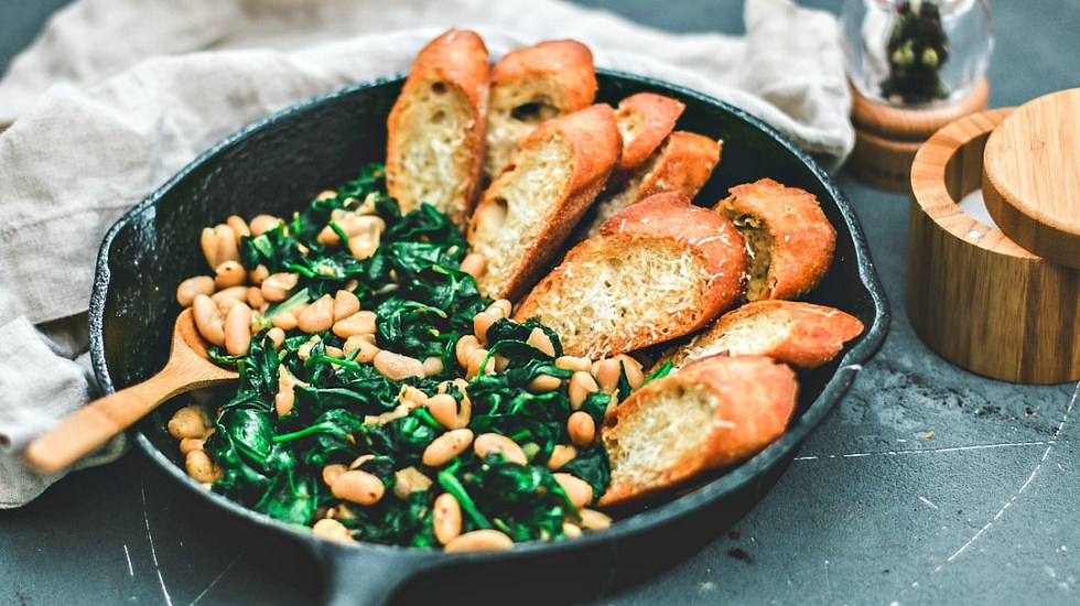 Close up of Beans and Greens in skillet lined with parmesan toasts.