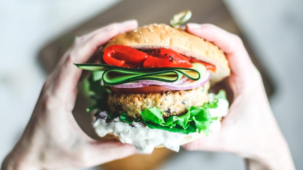 Close up of hands grabbing burger.