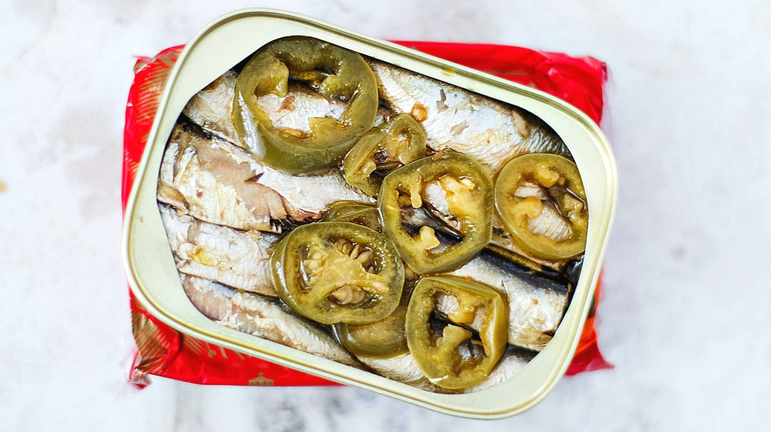 Opened can of King Oscar sardines with slices of jalapenos.