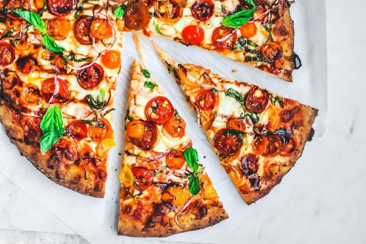 Bruschetta pizza slices pulled away from pizza.
