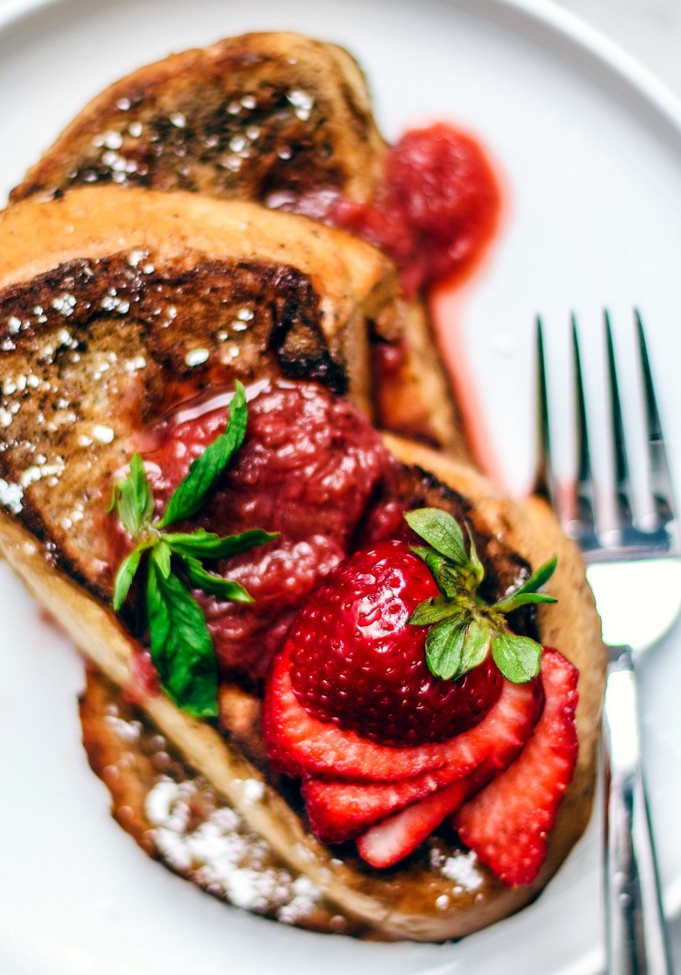 Close up of fresh strawberries fanned over French toast.