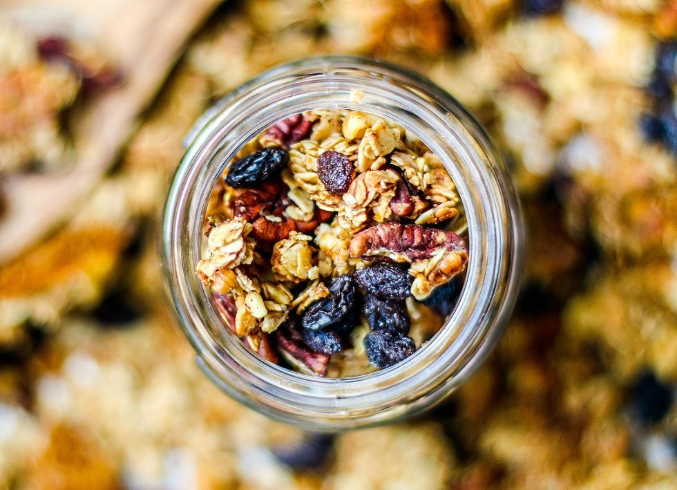 Homemade granola in a jar and scattered over a tray.