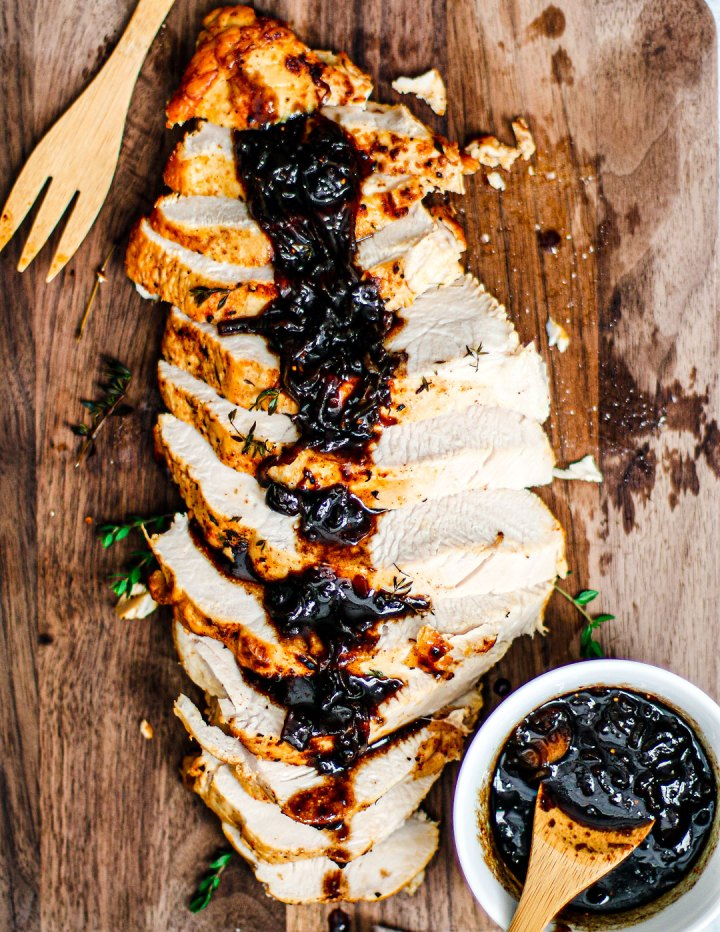 Overhead shot of roast turkey sliced on cutting board and topped with cranberry balsamic glaze.