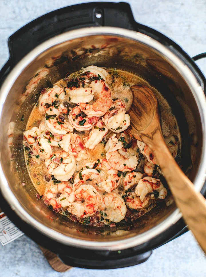 Overhead shot of cooked shrimp in garlic butter sauce inside the Instant Pot.