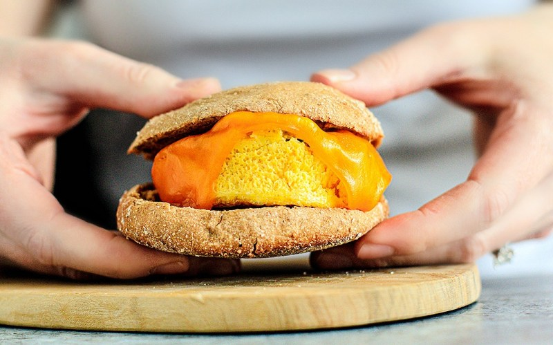 Hands holding cheesy egg muffin between English muffin bread.