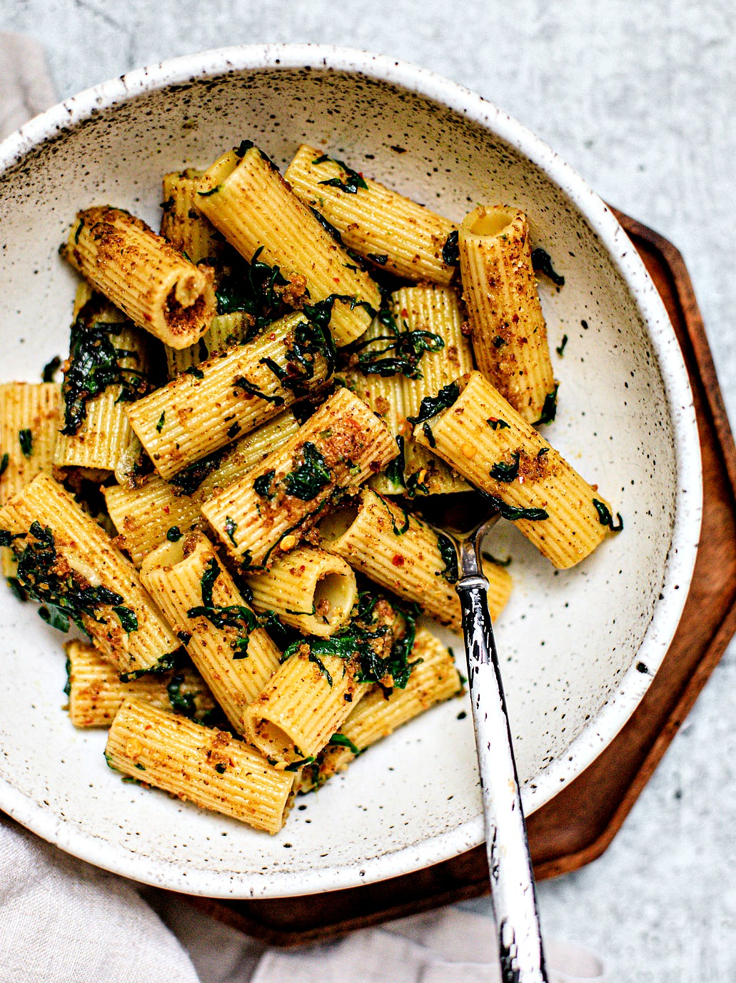 Close up of bowl full of garlicky rigatoni pasta with spinach.