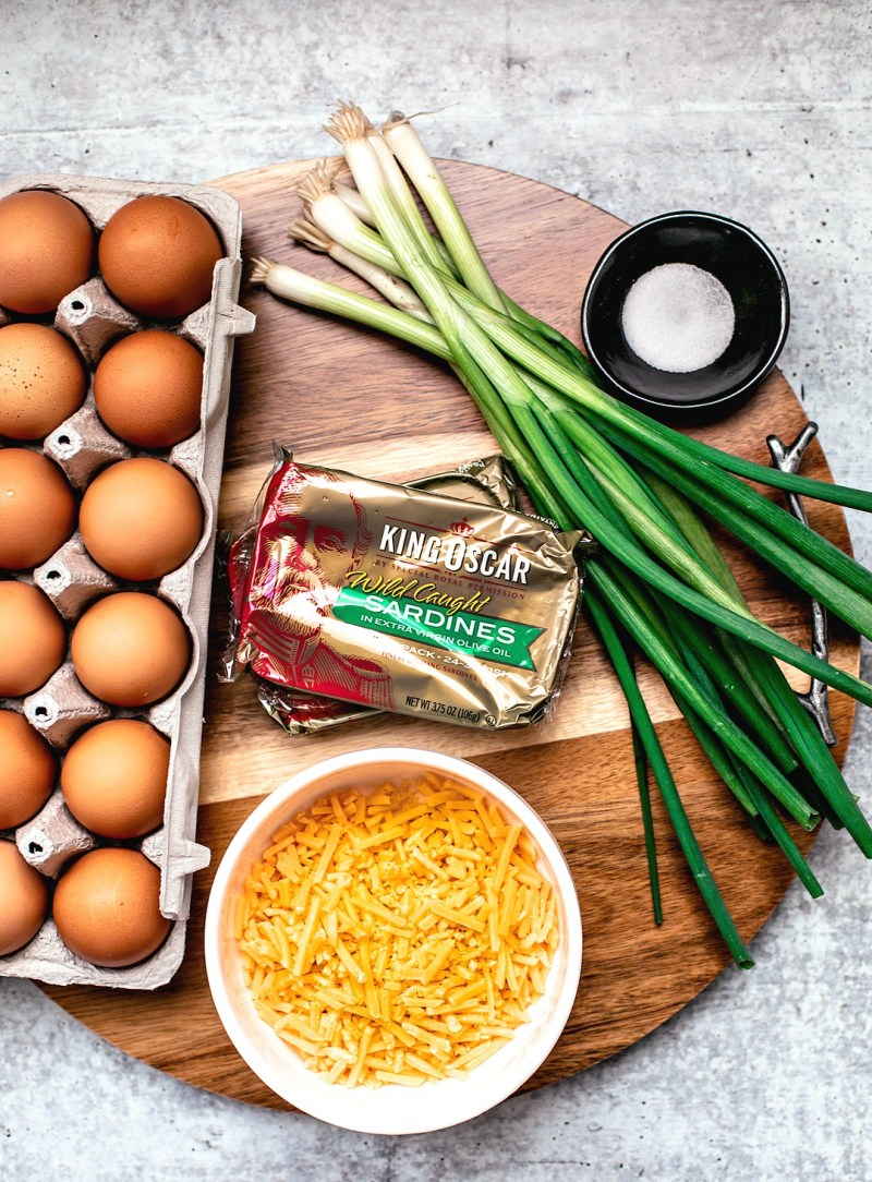 Ingredients for egg muffins on a round wooden board.