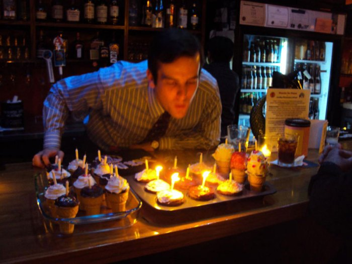 birthday boy blows out candles on cupcakes in ice cream cones