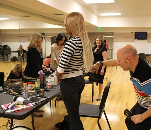 trimming blonde wig backstage at fashion for a cause kansas city