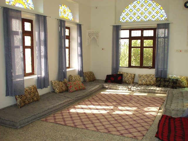 Stained glass qamarias adorn the windows in this Yemeni living room.