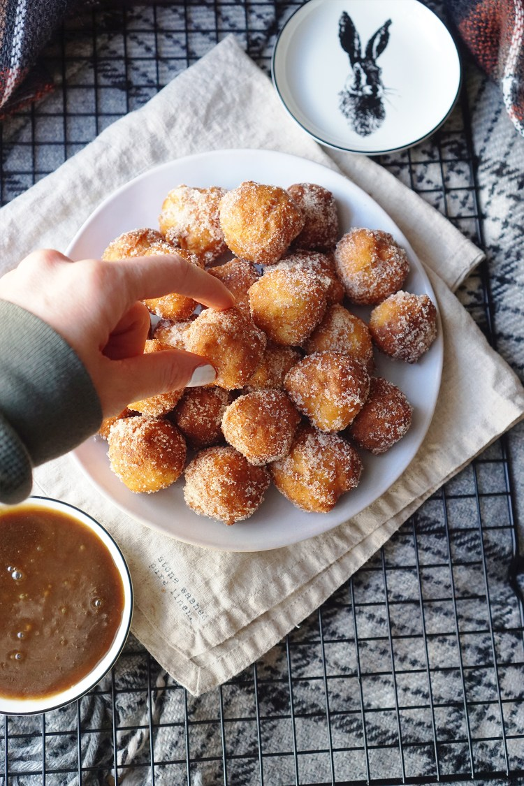 Gluten free churros donut holes rolled in cinnamon sugar with a homemade caramel sauce