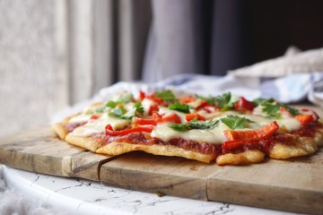 Crispy thin crust arepa pizza / gluten free pizza crust made with pre-cooked white cornmeal; topped with pizza sauce, roast chicken, sweet peppers, mozzarella and fresh coriander
