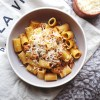 Classic Italian bolognese sauce with gluten free Pasta Rummo rigatoni and grated parmesan cheese