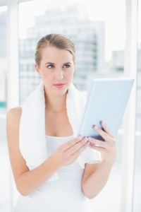 Thoughtful sporty woman in bright sports hall holding tablet pc