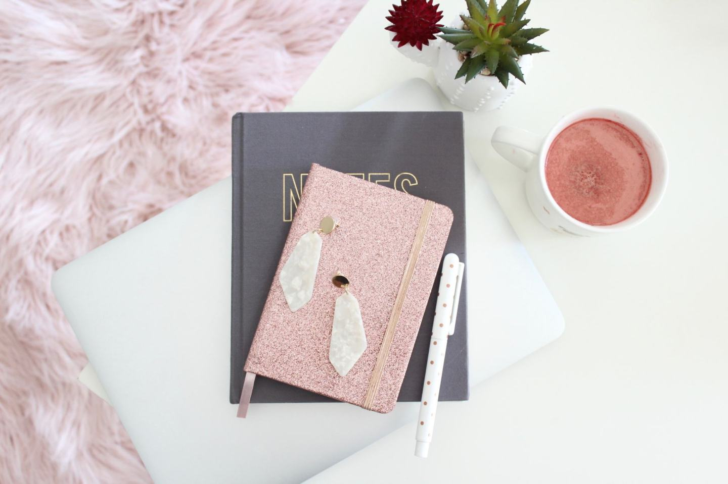 A rose gold stress diary on a white fur background