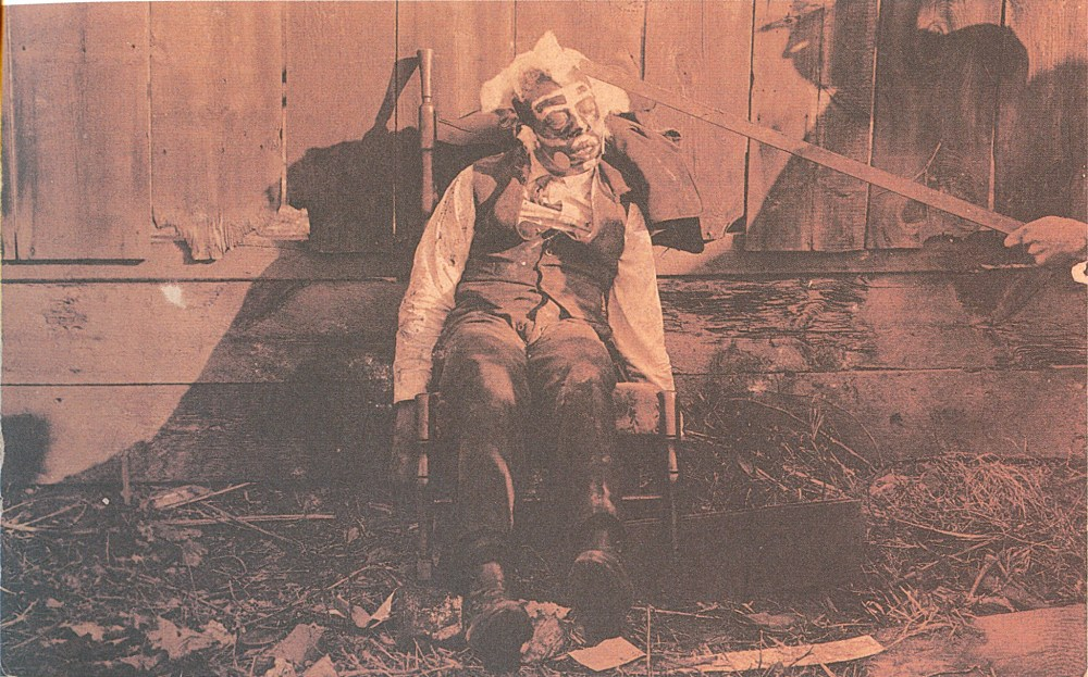 """The bludgeoned body of an African American male, propped in a rocking chair, blood-spattered clothes, white and dark paint applied to face, circular disks glued to cheeks, cotton glued to face and head, shadow of a man using rod to prop up the victim's head. Circa 1900, location unknown. Gelatin silver paint. Real photo postcard"