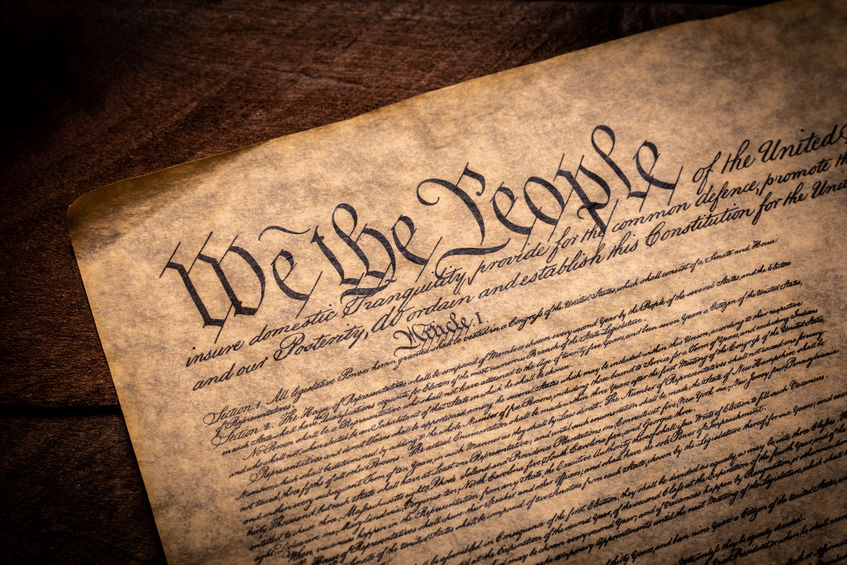 A copy of the Constitution of the United Sates of American on a wooden background